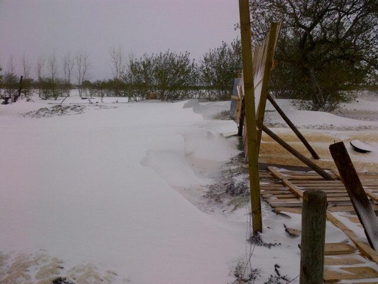 A damaged fence alongside substantial snow accumulation in MacGregor, MB.